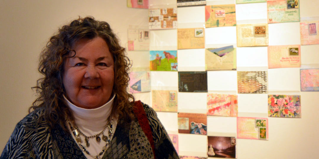 """Kathleen O'Brien with some of the 365 postcards """"Each Day in the Year of the Fire Dog"""" at Juxtapose exhibit"""
